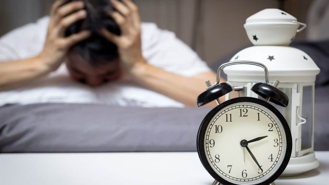 image of person who cannot sleep and alarm clock showing 2:25 AM
